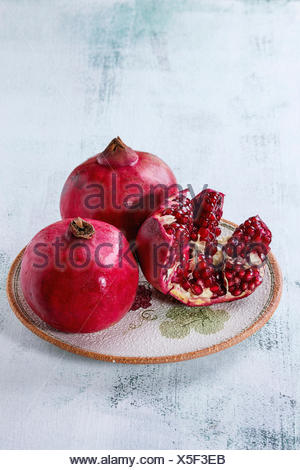 Ripe slice and whole pomegranates on ornate ceramic plate over white wooden background. - Stock Photo