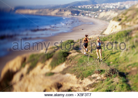 Women jogging on cliff along water - Stock Photo
