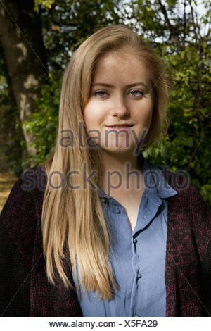 Smiling girl standing in forest - Stock Photo