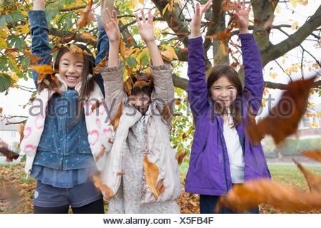 Portrait of three young girls throwing autumn leaves - Stock Photo