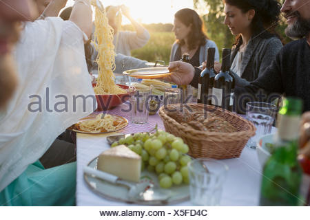 Friends serving pasta at garden party dinner - Stock Photo