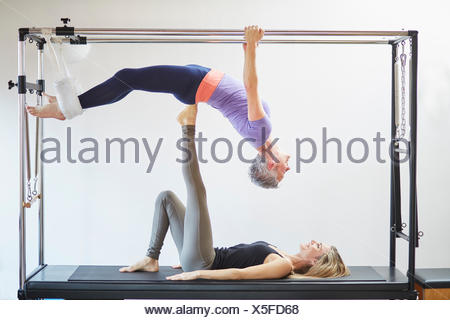 Two mature women practicing pilates on trapeze table in pilates gym - Stock Photo