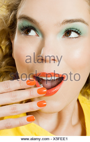 Surprised young blonde woman against yellow background - Stock Photo