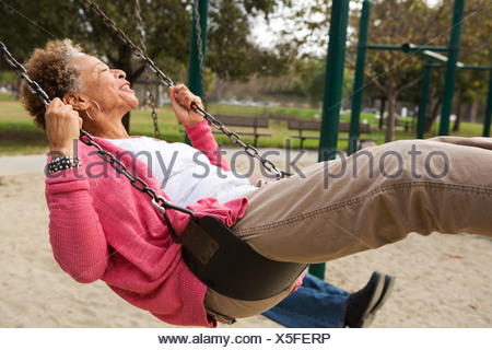 Senior woman on swing in park - Stock Photo