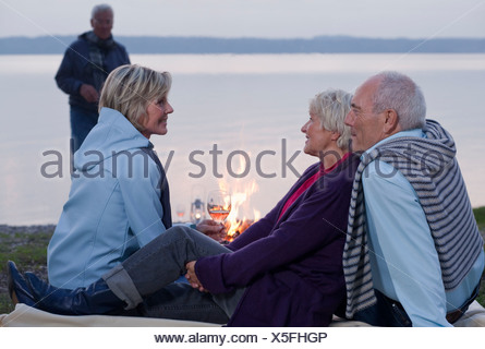 Two senior couples drinking wine and talking beside a campfire - Stock Photo