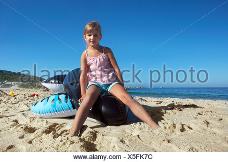 Girl 4 6 sitting on inflatable toy whale on beach smiling portrait - Stock Photo