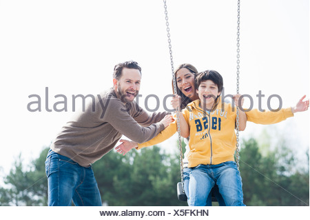 Parents holding up son on park swing - Stock Photo