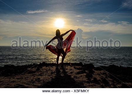 Woman Dancing On Cliff By Sea Against Sky During Sunset - Stock Photo