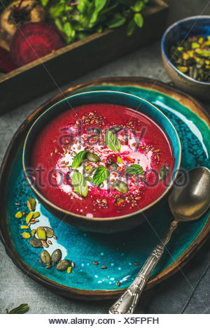 Spring detox red beetroot soup with mint, chia, flax and pumpkin seeds in blue ceramic bowl over grey concrete background. Dieting, clean eating, vega - Stock Photo