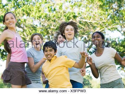 Preteen friends jumping, portrait - Stock Photo