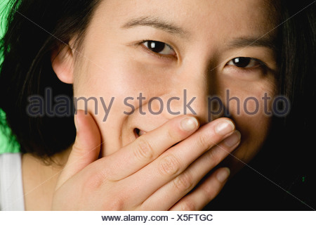Young woman covering mouth with hand, smiling, portrait - Stock Photo