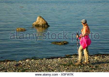 Hiker on beach, Fort Flagler State Park, Washington. - Stock Photo