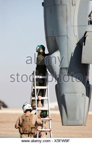 United States Marine Corps aircraft maintenance specialists working on engine housed inside engine nacelle MV-22 Osprey Camp - Stock Photo