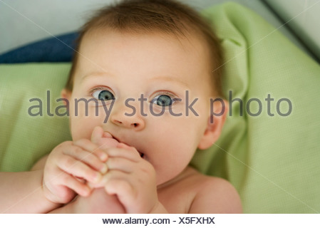 Baby with foot in mouth, close-up - Stock Photo