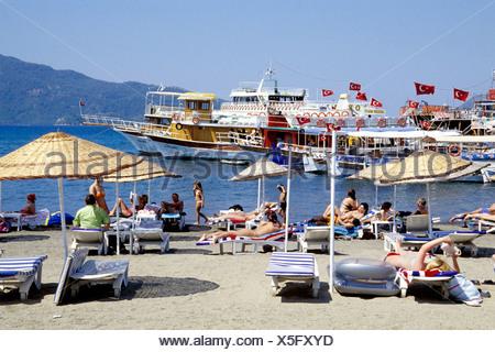 Tourist, sunshades and excursion boats at the beach, Marmaris in the Mugla Province, Mediterranean Sea, Turkey - Stock Photo