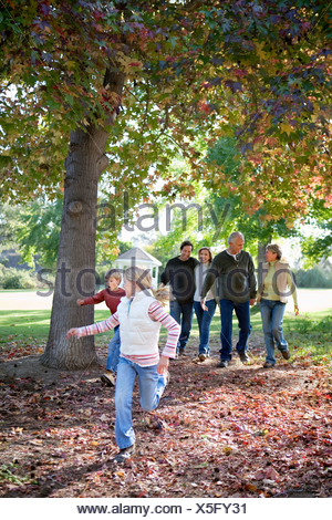 Multi generational family walking beside tree in park in autumn two children 6 9 running on ahead - Stock Photo