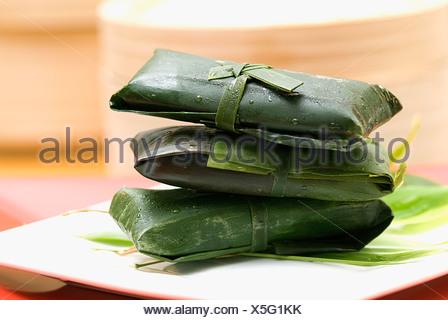 Rice dumplings wrapped in banana leaves - Stock Photo