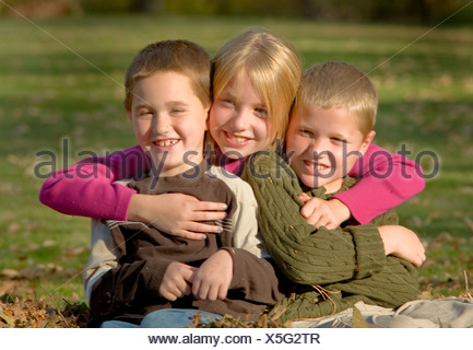 Children sitting in a pile of Autumn leaves - Stock Photo