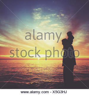 Silhouette of a boy sitting on his father's shoulders, Laguna beach, Orange County, California, USA - Stock Photo