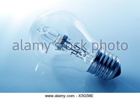 Energy-saving lamp on the blue background. - Stock Photo