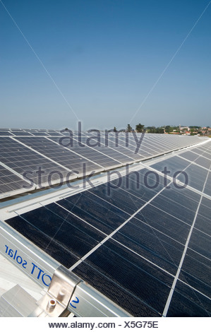 Electricity converting solar panels on a roof of a cowshed - Stock Photo