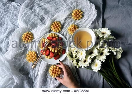 Woman's hand and breakfast waffles - Stock Photo