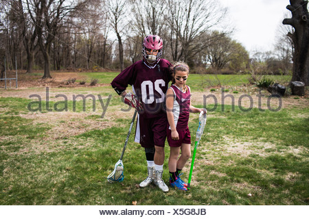 Brother and sister wearing lacrosse uniforms - Stock Photo