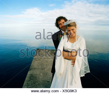 Scandinavia, Sweden, Oland, Groom and bride embracing on jetty, smiling, portrait - Stock Photo