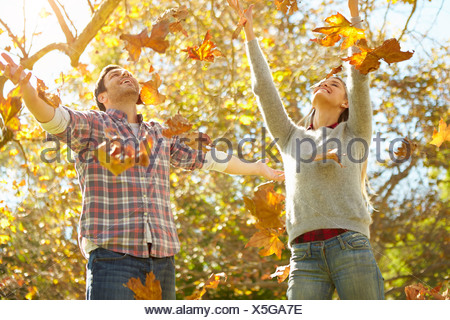 Couple Throwing Autumn Leaves In The Air - Stock Photo