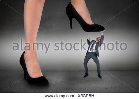Composite image of businesswoman stepping on tiny businessman - Stock Photo