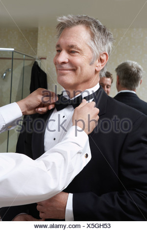 Young man tying middle-aged man's bow tie - Stock Photo