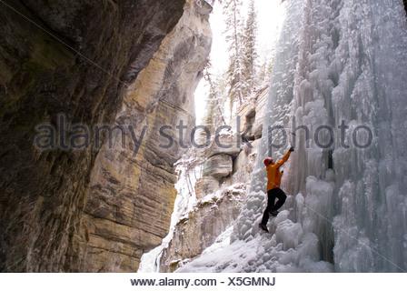 Female climber explores ice climbing in the narrows of Maligne Canyon in Jasper National Park, Alberta, Canada - Stock Photo