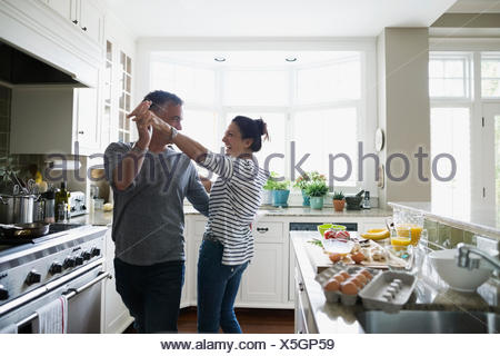 Playful couple dancing in kitchen - Stock Photo