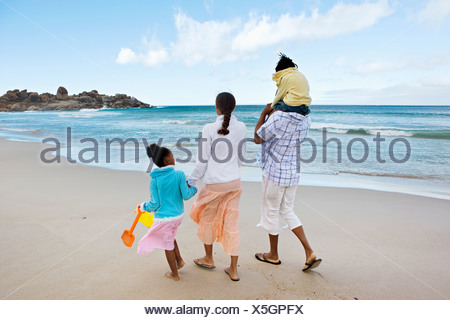 Two generation family walking along sandy beach girl 5 7 on father s shoulders rear view - Stock Photo