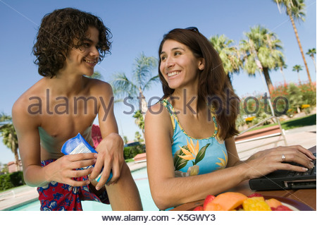 Mother and son (13-15) at swimming pool, mother using laptop. - Stock Photo