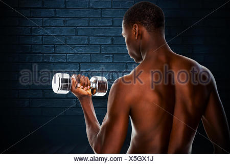 Composite image of rear view of a fit shirtless young man lifting dumbbell - Stock Photo