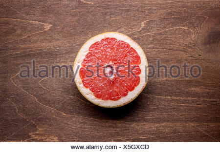 cut grapefruit on wooden background - Stock Photo