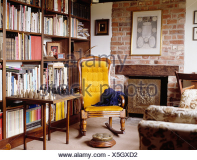 Yellow armchair and chess set on table in front of bookshelves in country living room with fireplace in exposed brick wall - Stock Photo