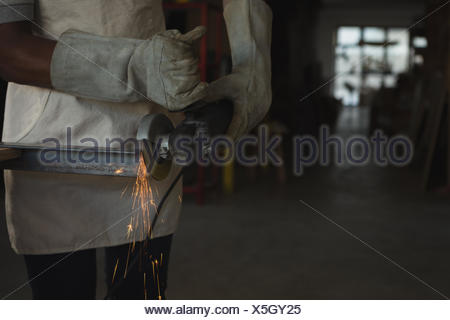 Carpenter cutting metal with electric saw - Stock Photo