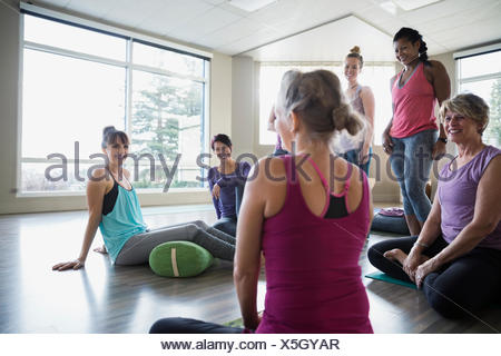 Instructor and students talking in restorative yoga class - Stock Photo