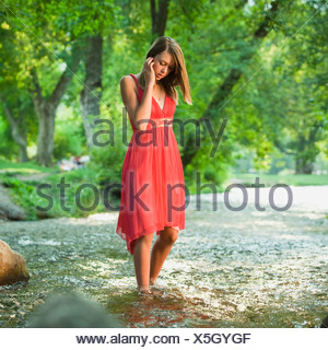 Portrait of woman standing in river - Stock Photo