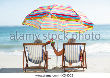 Cute mature couple lying on deckchairs - Stock Photo