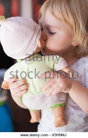 lovely and tender scene of blonde caucasian cute baby two years old kissing on the mouth a doll in hands indoor. - Stock Photo