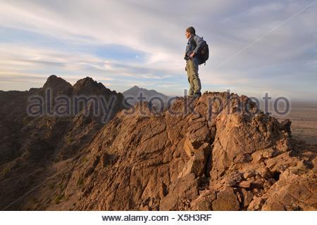 USA, Arizona, Mohawk Mountains, Climber on top of Mountain - Stock Photo