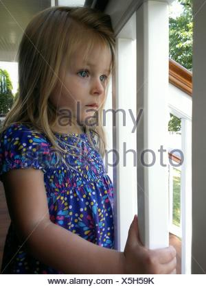 Close-Up Of A Cute Girl Looking Through Window - Stock Photo