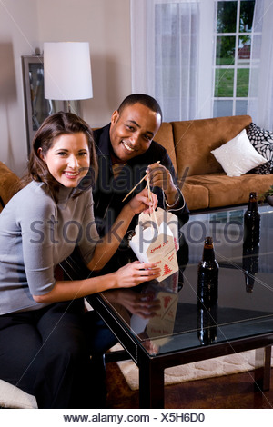 Multi-ethnic couple eating Chinese take-out in modern loft - Stock Photo
