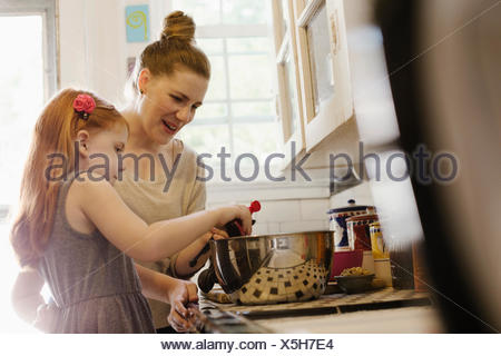 Mid adult mother giving daughter a helping hand in kitchen - Stock Photo