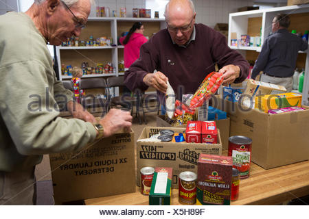 Volunteers pack boxes of donated food at the Mitchell County Food Bank in Osage Iowa. - Stock Photo