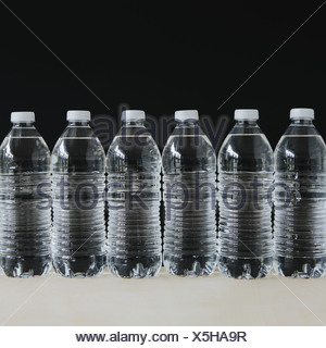 Row of clear, plastic water bottles filled with filtered water in a row, on a black background. - Stock Photo