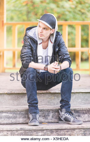 Young man wearing a leather jacket, sitting in a park - Stock Photo